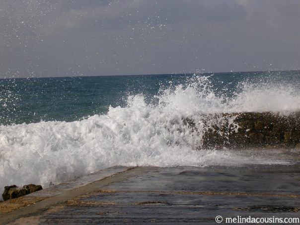 Waves crashing over part of Herod's breakwater wall