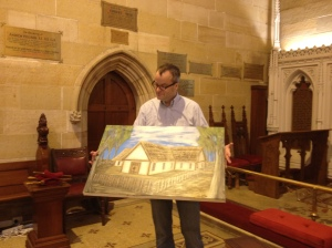 The current rector of St Phillips, holding a painting of the original St Phillips, built by Johnson at his own expense